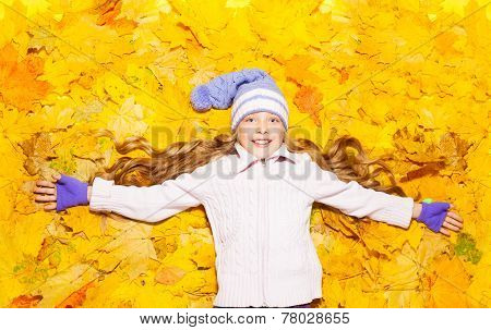 Happy little girl in autumn maple leaves