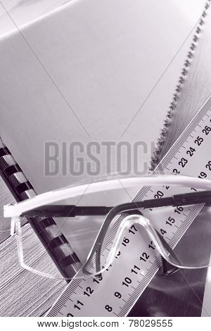 Ruler, Notebook, Handsaw And Goggles In Toning