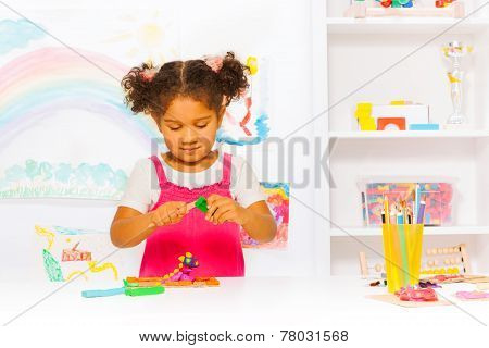 Preschool girl play with modeling clay in class