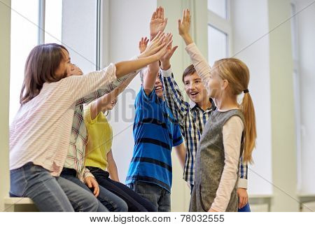 education, elementary school, children, gesture and people concept - group of smiling school kids making high five in corridor