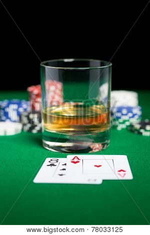 gambling, fortune and entertainment concept - close up of casino chips, whisky glass, playing cards and cigar on green table surface