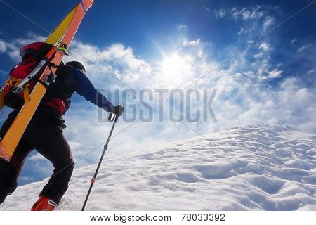 Ski mountaineer walking up along a steep snowy ridge with the skis in the backpack. In background a dramatic sky. Concepts: adventure, achievement, courage, determination, extreme sport