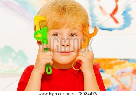 Close portrait of boy with working toy tools