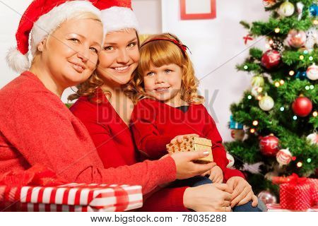 Granny and mother give presents to 3 years girl