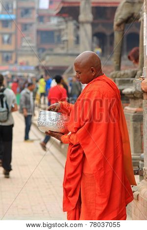 KATHMANDU, NEPAL - APRIL 2014 : A Buddhist monk counting donated money from tourists and locals in the Durbar Square, Central Kathmandu, Nepal on 13 April 2014.