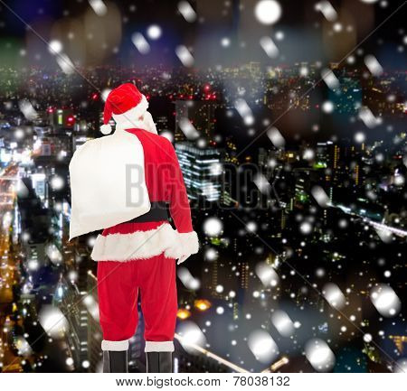 christmas, holidays and people concept - man in costume of santa claus with bag from back over snowy night city background