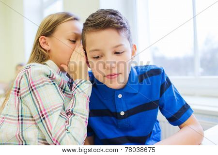 education, elementary school, learning and people concept - smiling schoolgirl whispering secret to classmate ear in classroom