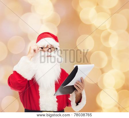 christmas, holidays and people concept - man in costume of santa claus with notepad over beige lights background