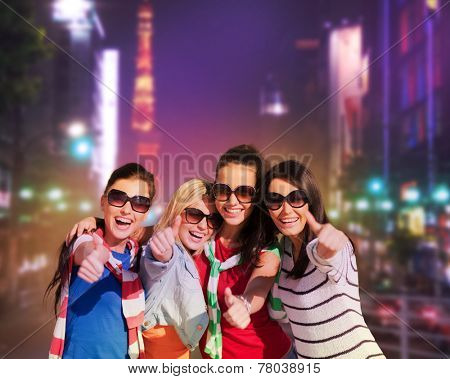 summer, holidays, vacation, happy people concept - beautiful teenage girls or young women showing thumbs up in night city street