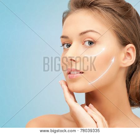 beauty, plastic surgery, aging, people and health concept - beautiful young woman touching her face with lifting arrows over blue background