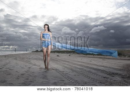 Pretty Model Holding Long Blue Dress On The Beach. Windy And Cloudy Summer Weather