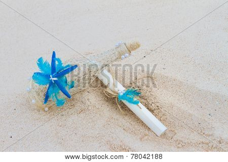 decorated glass bottle and paper letter note on tropical sand beach