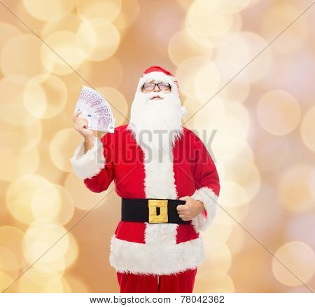 christmas, holidays, winning, currency and people concept - man in costume of santa claus with euro money over beige background