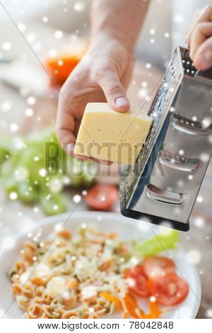 cooking, food, people and home concept - close up of male hands with grater, vegetables and pasta grating cheese in kitchen