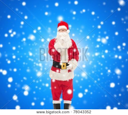 christmas, holidays and people concept - man in costume of santa claus making hush gesture over blue snowy background