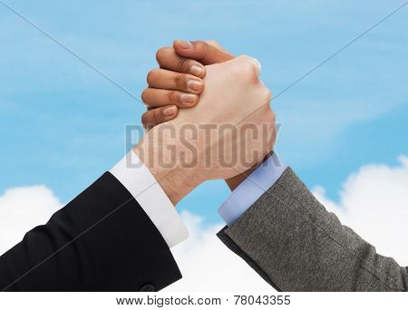 business, people and competition concept - close up of two people hands arm wrestling over blue sky and white cloud background