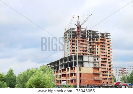 Unfinished Apartment Building With Brick Walls And Crane At Summer