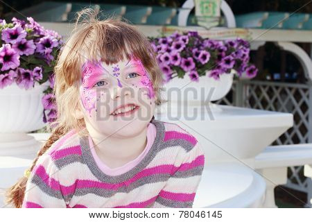 Happy Little Girl With Pictured Purple Butterfly On Face Near Pots Of Flowers Outdoor