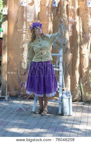 Perm, Russia - Jun, 23, 2014: Woman With Cage At Show Of Perm Puppet Theater In Gorky Park