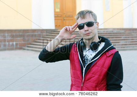 Young Man In Red Vest And With Headphones Salutes On Street At Spring Day