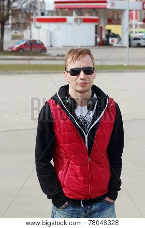 Young Man In Sunglasses And Red Vest Stands On Street At Spring Day