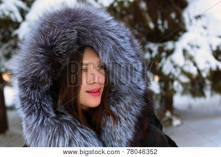 Beautiful Girl In Fur Coat With Hood Stands Near Big Snowy Spruces In Winter Forest
