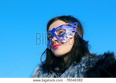 Girl In Fur Coat And Mask Looks Away In Sunny Winter Day