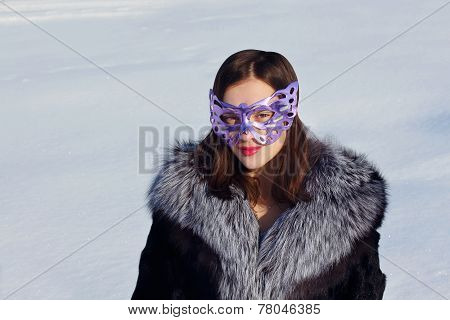 Girl In Fur Coat And Mask At Background Of Snow