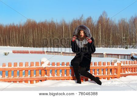 Beautiful Girl In Fur Coat With Hood Sits On Wooden Fence In Winter