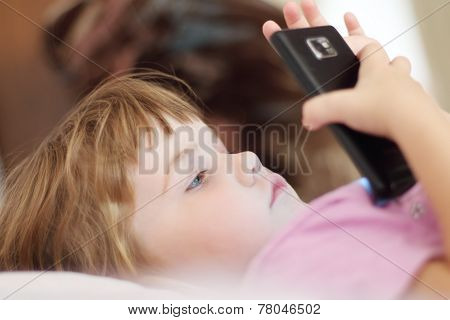 Little Serious Beautiful Girl In Pink Lying With Touch Phone. Shallow Dof