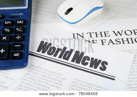 On-line news and business concept. Computer mouse, calculator and newspaper on wooden table background