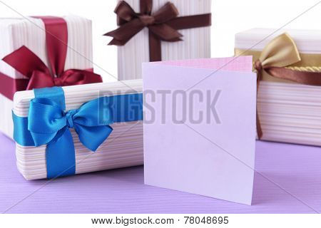 Cute presents with greeting card on light blue uneven surface isolated on white