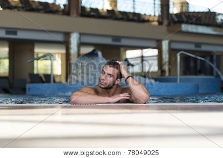 Young Man Swimming In Pool At Resort