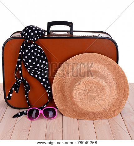 Vintage valise with summer items on wooden board