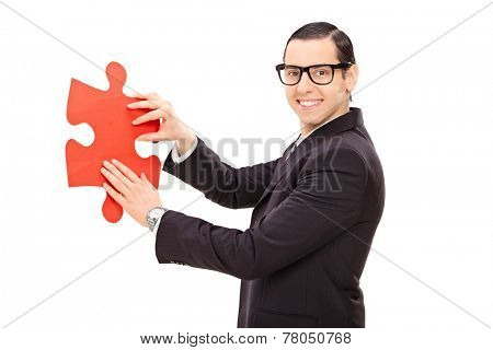 Young businessman holding piece of a puzzle isolated on white background