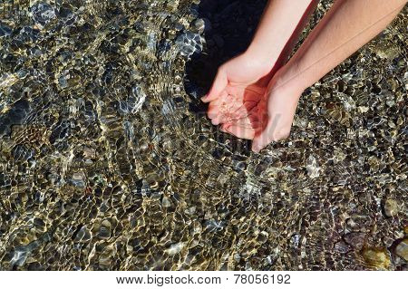 Beautiful woman hand in clear mountain water