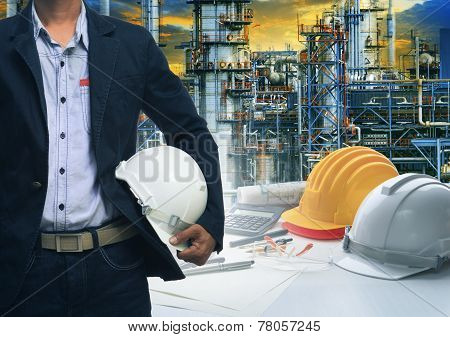 Engineering Man Standing With White Safety Helmet Against  Oil Refinery In Petrochemical Industry
