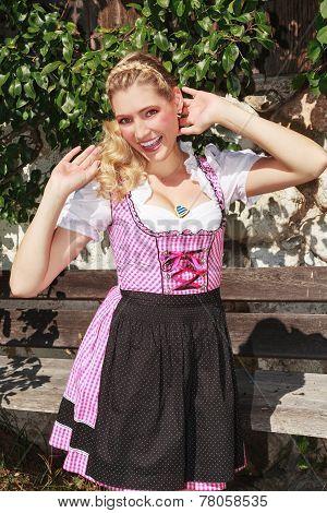 Flirty blond bavarian girl in dirndl