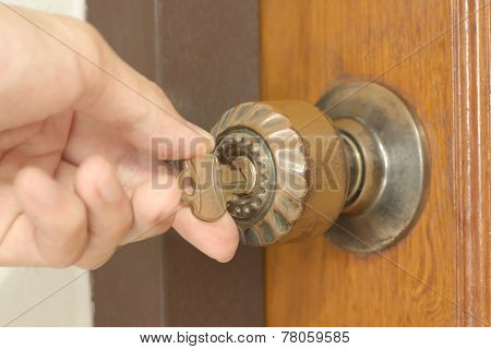 Closeup of male hand unlocking old door knob