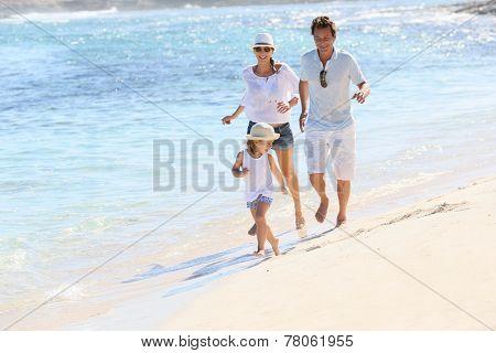 Family running on a white sandy beach