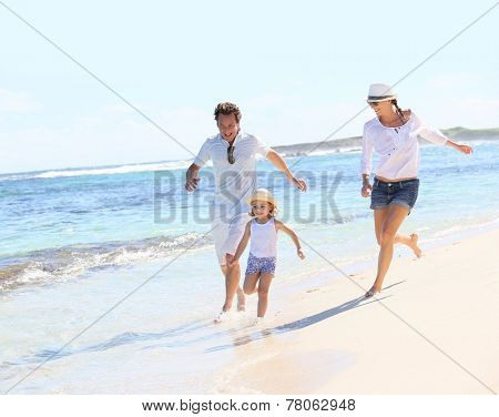Couple with little girl running on Caribbean beach