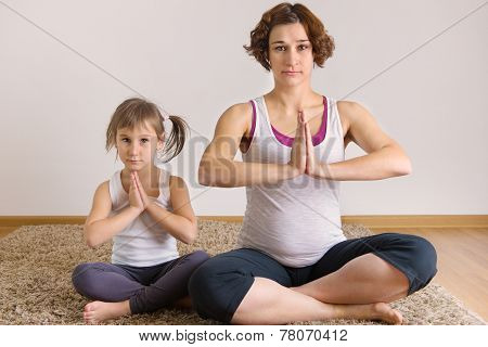 Pregnant Woman And Little Daughter Yoga Exercising