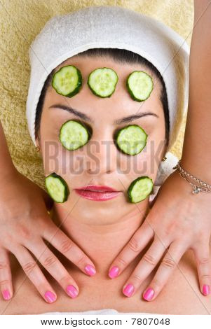 Woman With  Cucumber Mask Getting Neck Massage