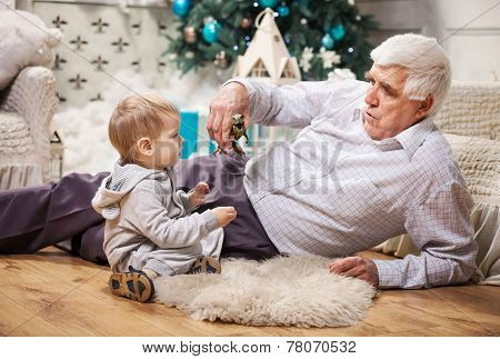 Toddler boy and his grandpa playing with toy