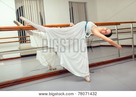 Beautiful classic ballet dancer in white tutu posing on one leg next to handle bar.