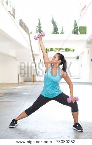 Beautiful hispanic sport woman doing side lunge with two pink dumbbell outdoor. Concept of healthy lifestyle.