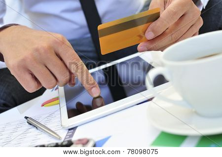 a young man in suit shopping online with a credit card via a tablet computer