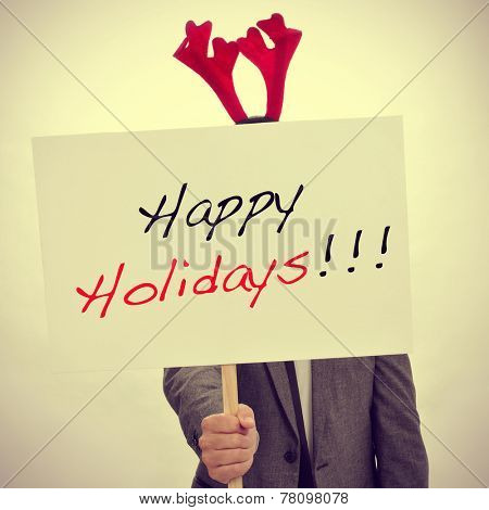 a man in suit with a reindeer antlers headband showing a signboard with the text happy holidays written in it, with a filter effect