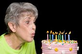 picture of inference  - A senior female blows out candels on a cake - JPG