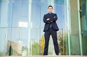 stock photo of laws-of-attraction  - Full length portrait of an attractive young Latin businessman standing in front of a building - JPG